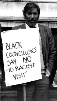 Man with plackard saying Black Councillors say no to racist visit